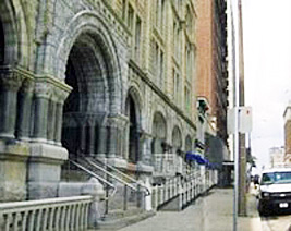 Accessibility ramp installed at grade along the side entrance of a Richardsonian Romanesque Style building