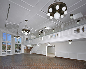 Interior of a former auto showroom showing the view from the mezzanine looking toward the upstairs balcony railing that extends the length of the room, with brick flooring, white painted woodwork, detailed celing with white globe chandeliers