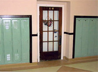 Exterior View: Retention of glass doors along historic corridor by incorporating new, code compliant doors on the interior.