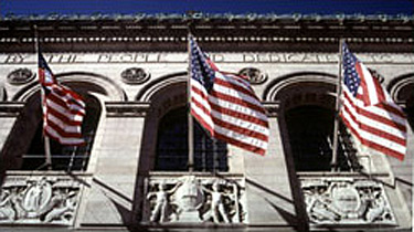 Photo of a building facade with carned details and three American flags