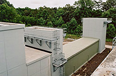 Photo of precast lightweight concrete for the outer square shell of the augmenter lined with acoustical pillows and perforated stainless steel inner panels