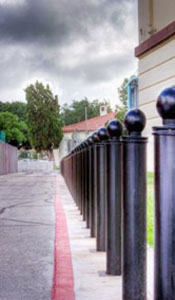 row of removable black bollards with a ball style top along roadway/sidewalk with red line road markings