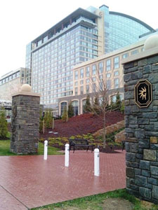 Image of the front of Gaylord National Hotel and Convention Center, National Harbor, MD with white bollards along brick path between stone pillars and hotel in background