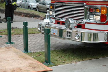 three collapsible by apparatus bumper force bollards with a fire truck about to knock into them
