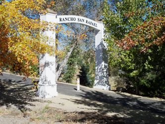 Entry to of Rancho San Rafael in Reno, Nevada with a single white bollard in the center of the roadway