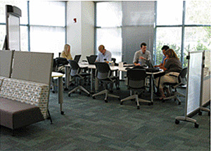 A long table positioned along a wall of windows and separated from workstations where workers are meeting in a small group at one end and individuals are working on their laptops on the other end