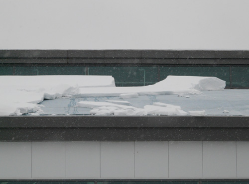 Snow breaking off and sliding from a roof
