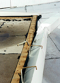 edge nailer lifted due to the gutter uplift load causing a progressive peeling failure of the roof membrane