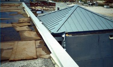 Photo of a metal roof over a stair tower where the irregularity created by the stair tower caused turbulence that resulted in wind speed-up