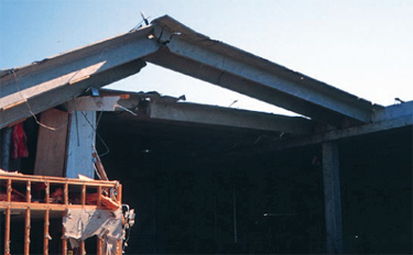 Photo of a precast twin-Tee roof where several of the roof and wall panels collapsed because of combined effects of wind uplift and pretension