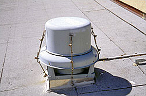 Cowling attached to the curb with cables to overcome blow-off of the fan coiling