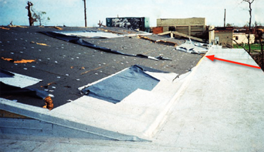 Photo of a building where a missile struck the fully adhered low-sloped roof and slid into the steep-sloped reinforced mechanically attached single-ply membrane