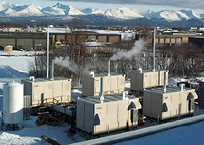 Photo of a mail processing center in Anchorage, Alaska. The photo shows five 200 kilowatt phosphoric acid fuel cells with mountains in the background.