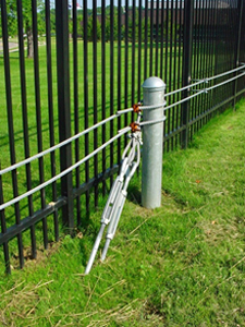 Tall black fence with a vehicle catch cable system shown in the grass in front of it