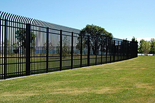 Long view of a vehicle barrier fence surrounding a grassy area