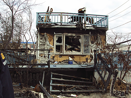 House showing the effects of wind and flood damage leading to fire