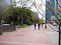 Two pedestrians walking along a wide path with a heavily raised planted berm on the left side to protect the courthouse beyond