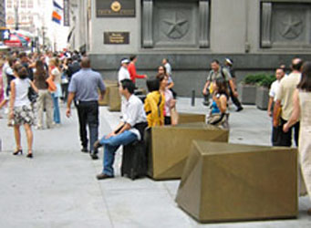Sculptural bollards with people seated on them and pedestrains walking past in the Wall Street financial district
