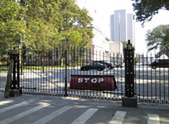 Entrance gate with a rotating wedge vehicle barrier displaying the word stop