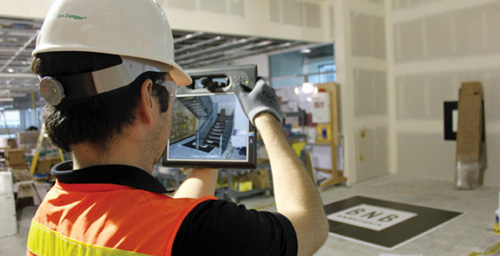 Worker using an electronic to monitor interior construction