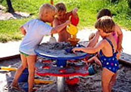 group of children playing at a sand table