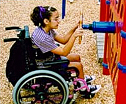 Photo of a child seated in wheelchair on a playground playing with an activity board
