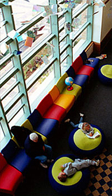 The children's area of Des Plaines Public Library featuring a wall of windows