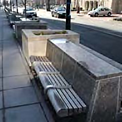 hardened site furniture-a bench for seating facing away from the street built on the backside of a planter along the curb