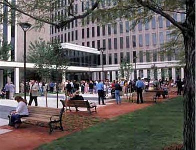 a plaza outside an office building where people are gathered standing along the sidewalks and sitting on the benches amongst the landscaping