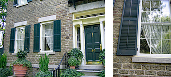 2 photos: on left is the view of the front of a 19th century brick house showing the black front door and two windows off to the left side with potted plants in the front; on the right a close up view of a black shutter and window on a 19th century brick house. The historic storm windows protect the original windows.